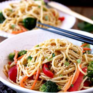 Pictured here is a big white bowl filled with Peanut Sesame Noodles with shredded carrots, sliced red bell peppers, broccoli florets, scallions and sesame seeds on a dark brown surface.