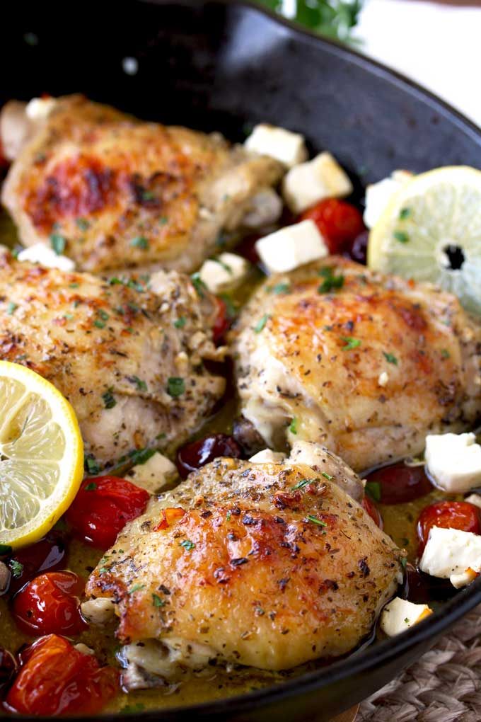 Greek Lemon Oven Roasted Chicken Thighs in a cast iron skillet with roasted tomatoes, Kalamata olives and Feta cheese