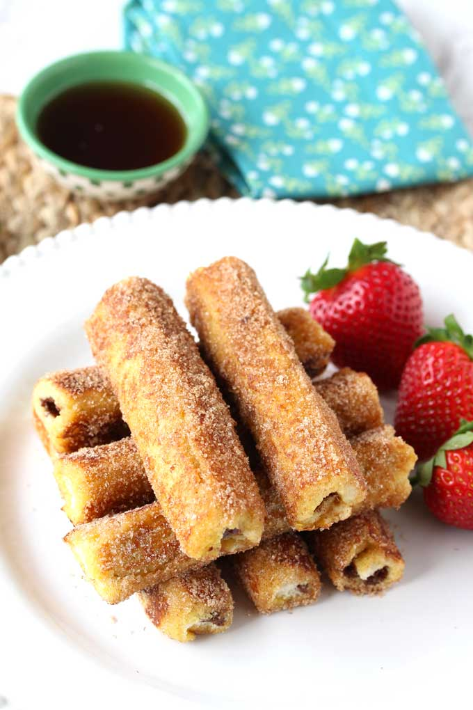 Stack of Nutella French Toast Roll-Ups on a white plate garnished with strawberries