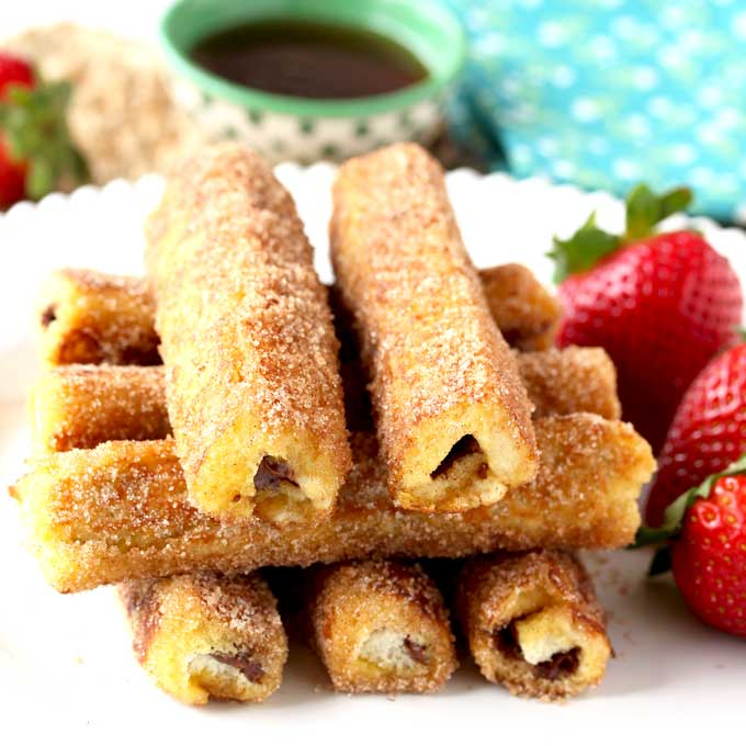 These Nutella French Toast Roll-Ups are a fun, finger-friendly treat for breakfast or brunch. These portable, and easy to make French Toast Roll Ups are filled with delicious Nutella, dunked into custard, sauteed until golden brown and then rolled in cinnamon sugar goodness!