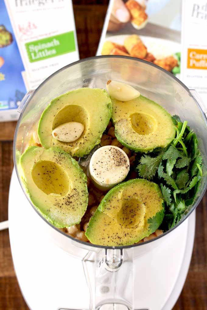 Ingredients for creamy avocado hummus in a food processor.