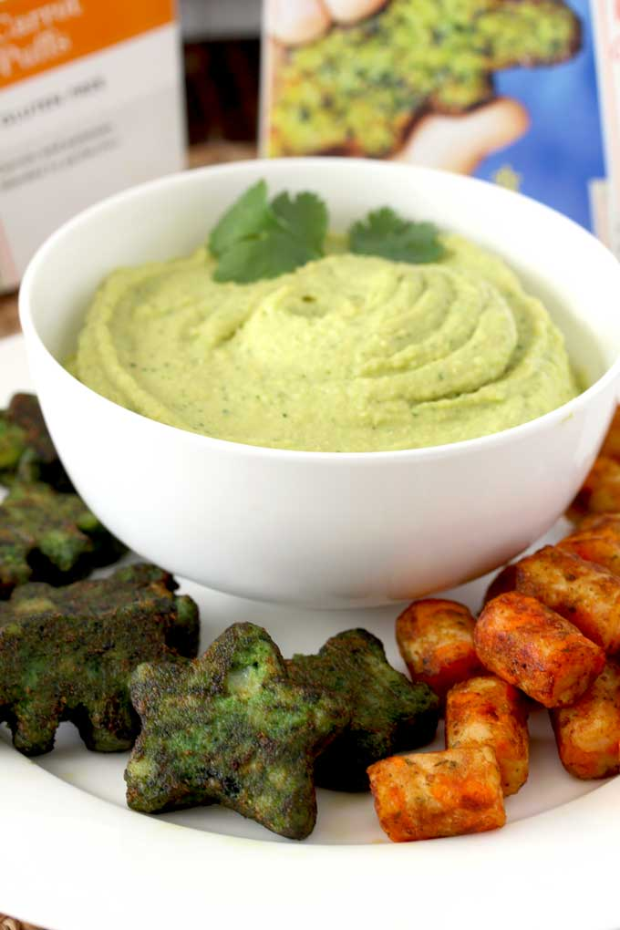 A big white bowl filled with creamy Avocado Hummus. Veggie stars and carrot tots are on a plate as dippers
