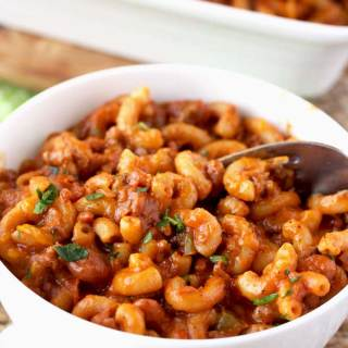 Creamy and Cheesy One Pot Chili Mac and Cheese on a white bowl scooped with a spoon.