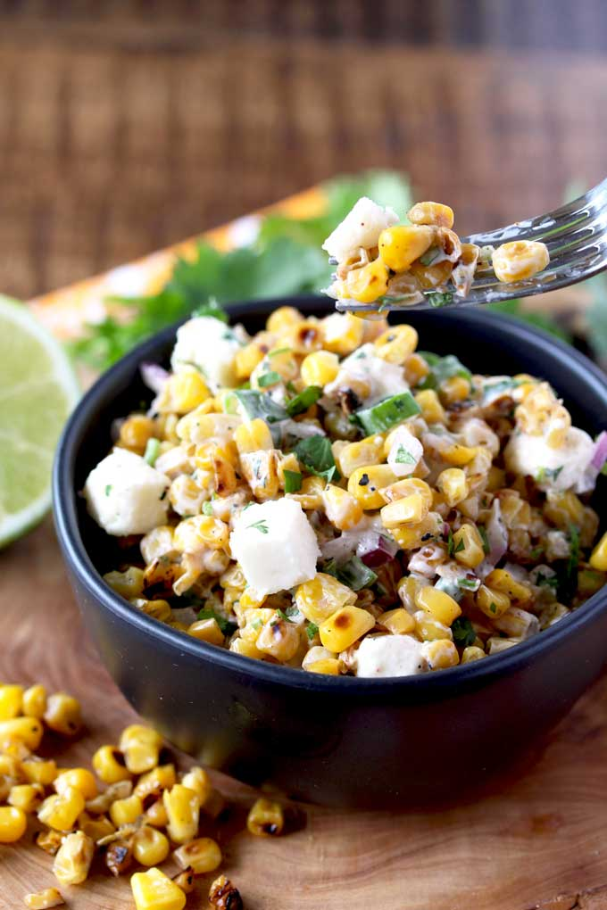 Fork scooping Mexican Street Corn Salad from a bowl