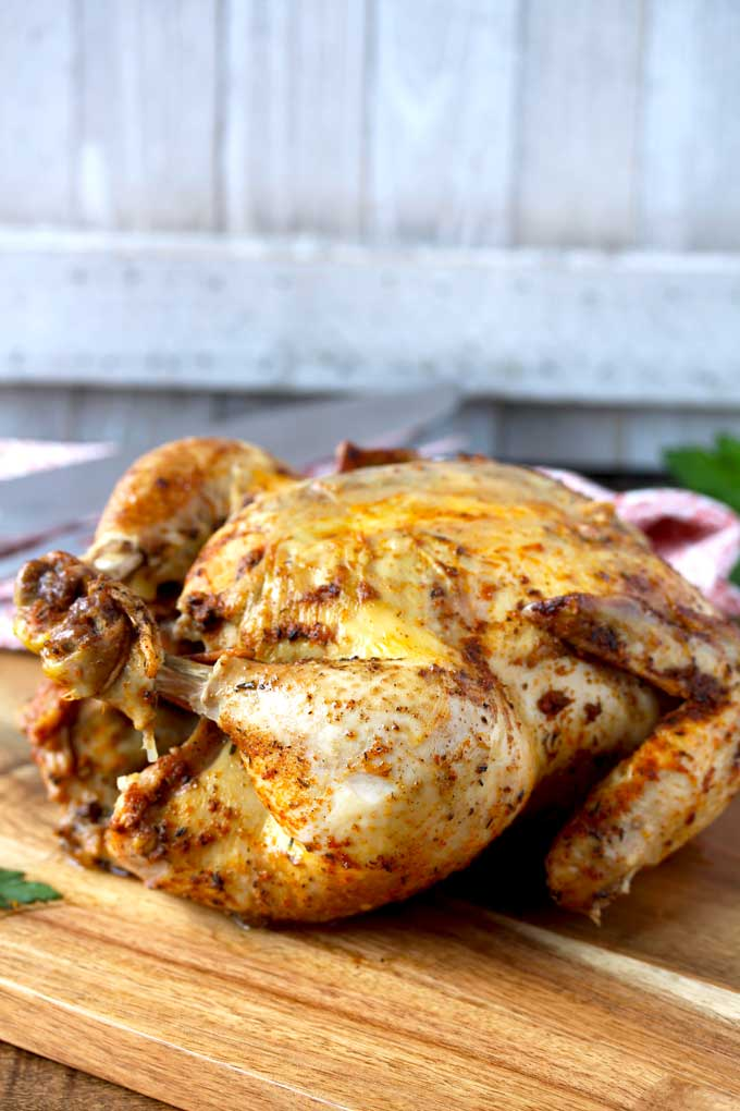 A whole chicken cooked in the instant pot on a wooden board