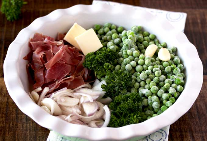 A white plate containing the ingredients to make sauteed peas with prosciutto and shallots. Butter, frozen peas, prosciutto, shallots and chopped parsley.