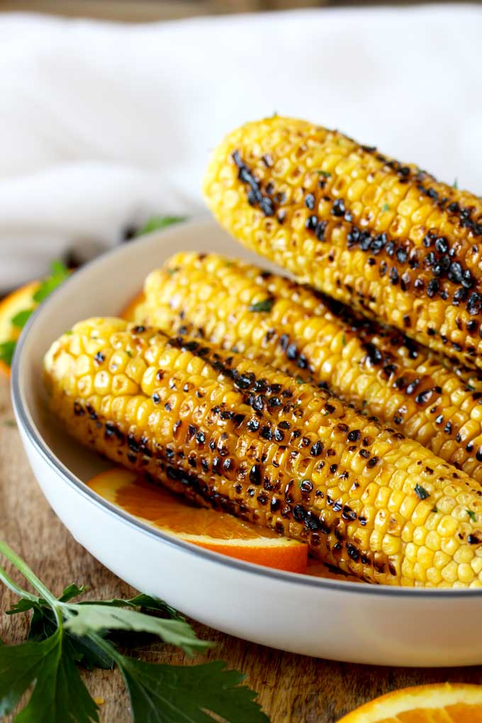 A stack of grilled corn on the cob on a white plate