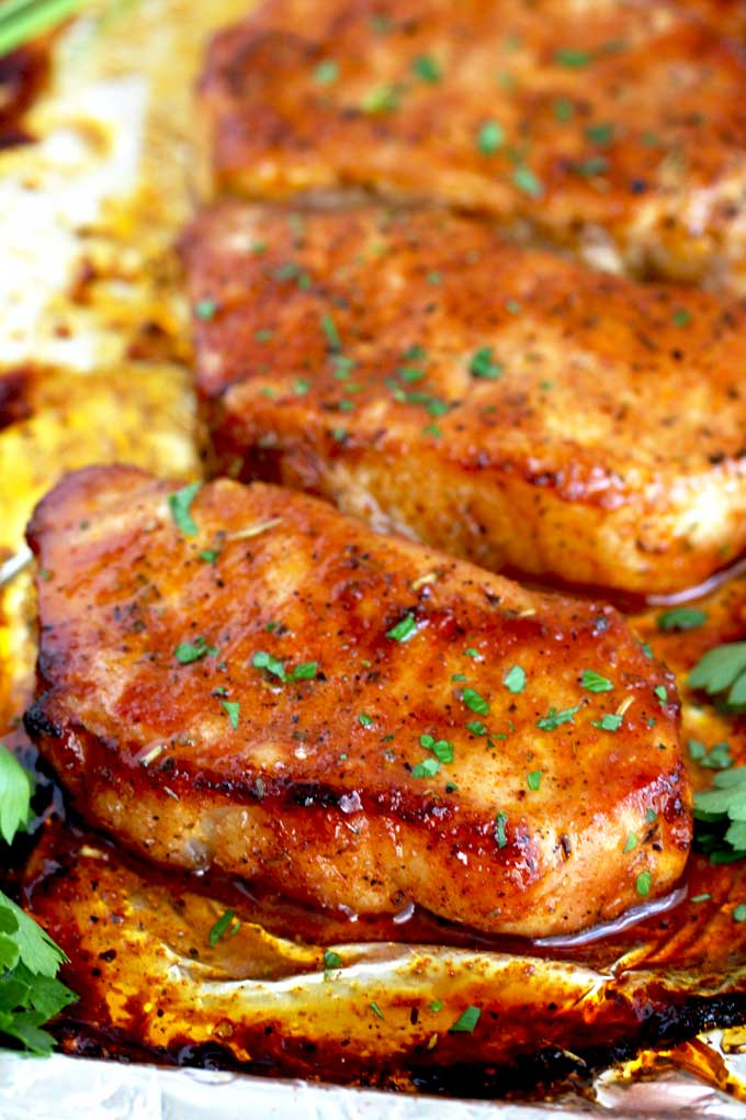 Several golden and juicy pork chops on a sheet pan coming out from the oven.