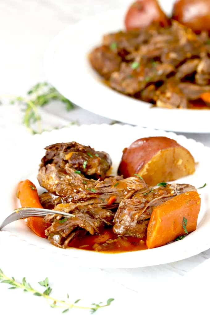 Shredded beef with carrots and potatoes on a white plate.