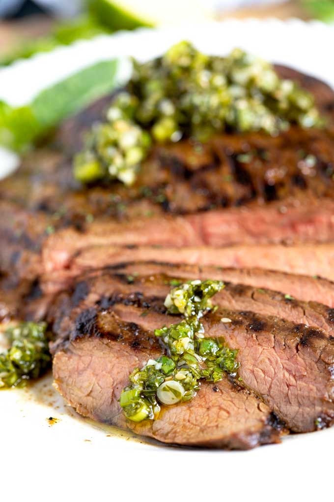 Close up view of sliced grilled steak topped with cilantro basil Asian chimichurri.