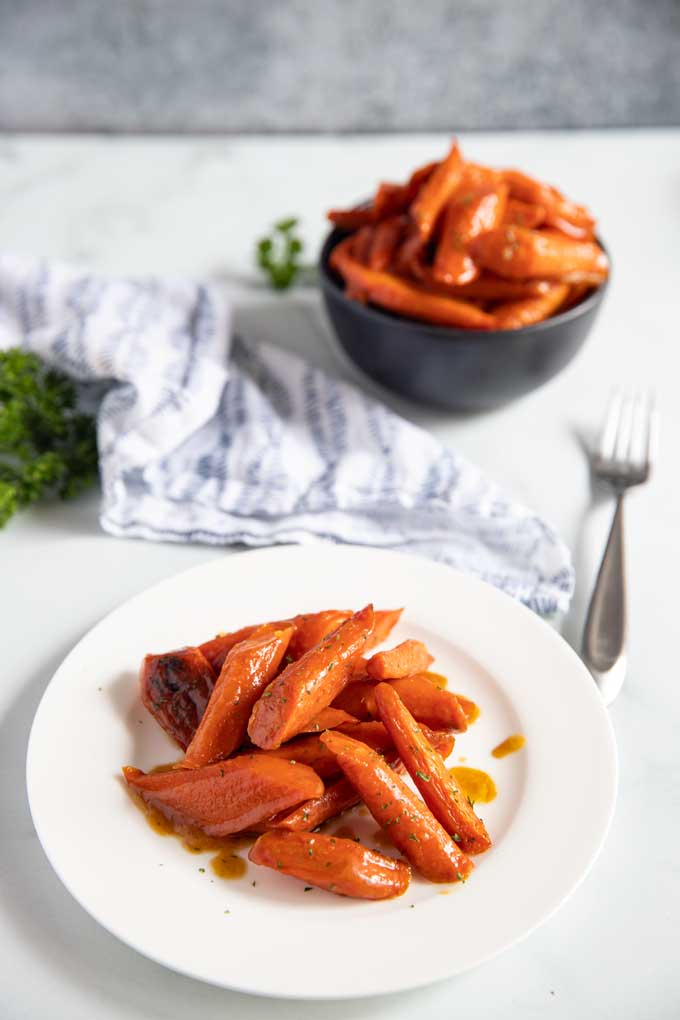 Two servings of oven baked carrots on a white plate and a black bowl.
