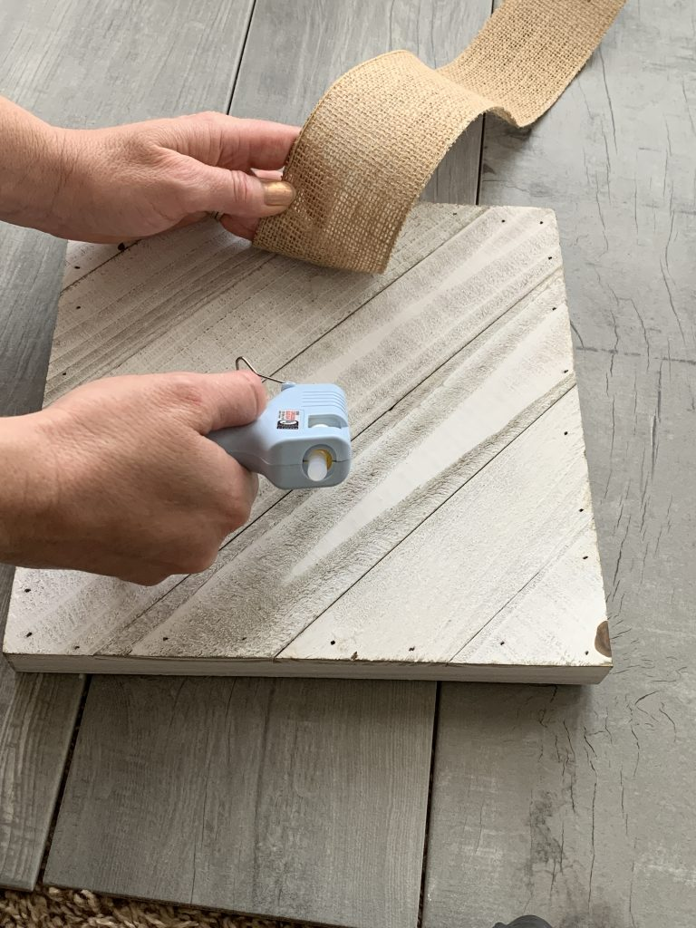 hot glue gun with white wood board burlap
