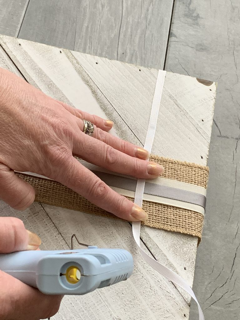 hand pressing ribbon on white board with hot glue gun