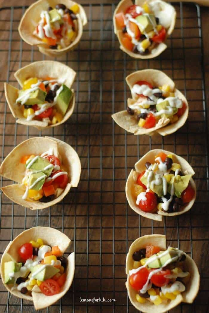 Mini tortilla cups fill with veggies and a dollop of taco cream cheese www.lemonsforlulu.com