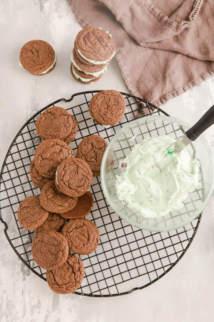 sandwich cookies on a baking rack with frosting