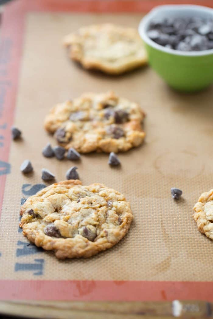 Three delicious Butterfinger cookies on a cookie tray with chocolate chips.