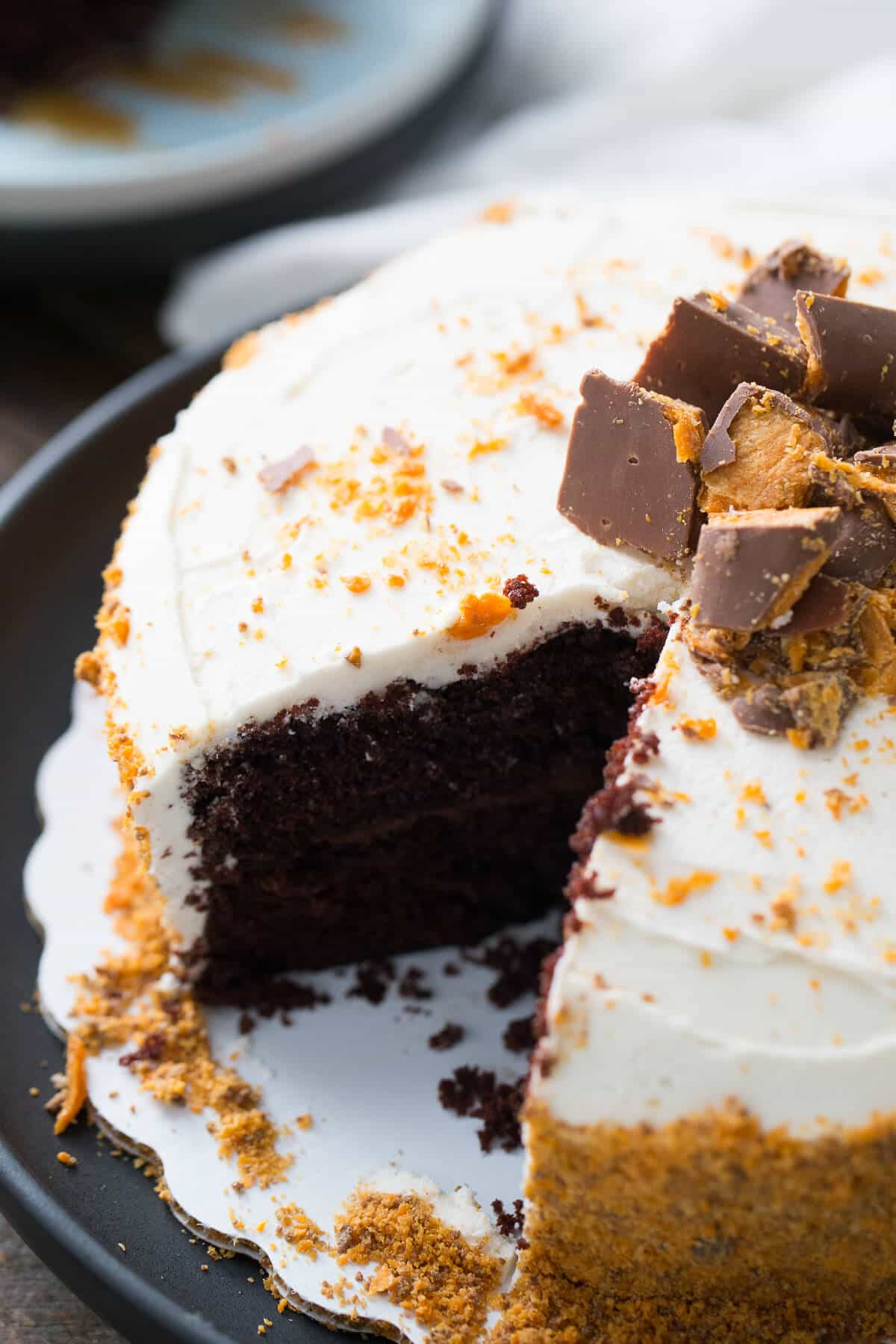 This Butterfinger cake is two layers of decadence! A rich chocolate cake is layered and filled with chocolate ganache and topped with Buttercream and Butterfingers!