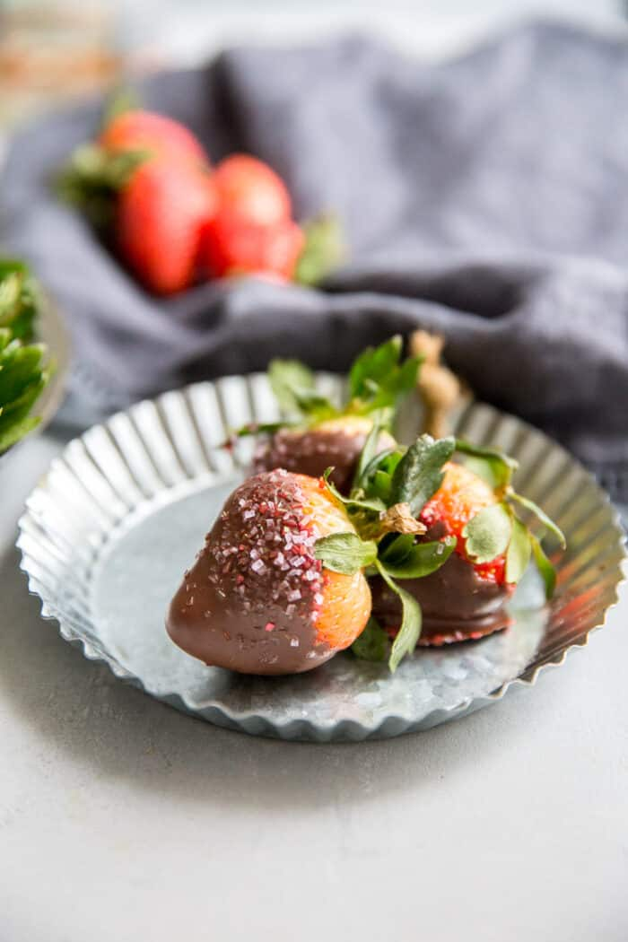 three chocolate covered strawberries on a silver plate