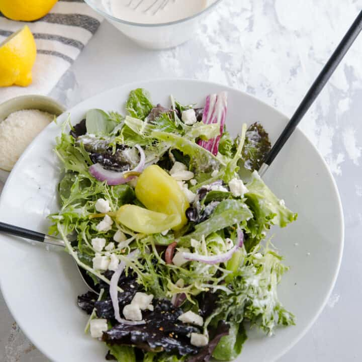caesar salad tossed with salad tongs