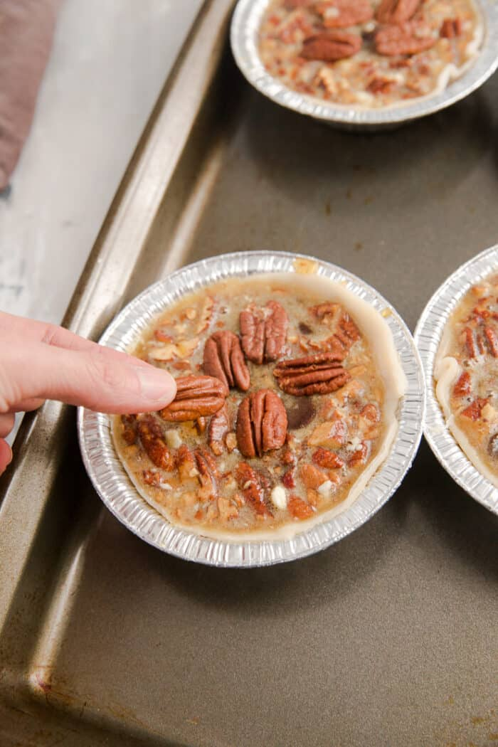 placing a pecan on an unbaked pie