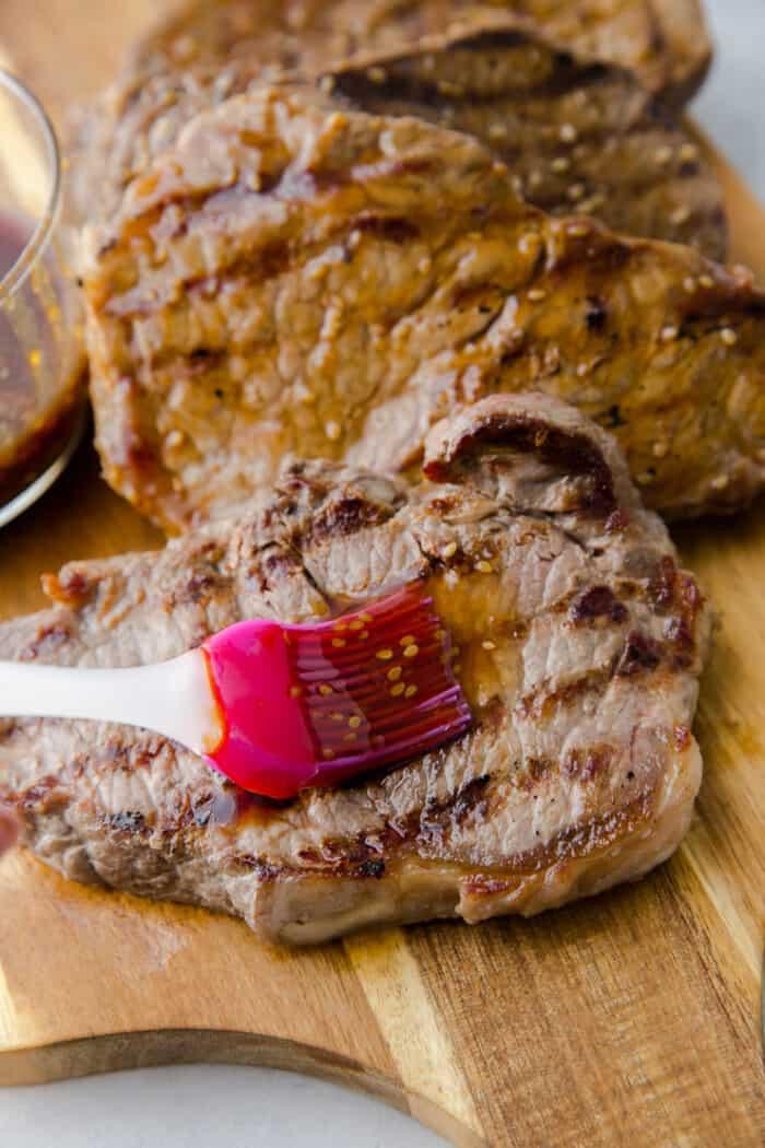 brushing steak with sauce