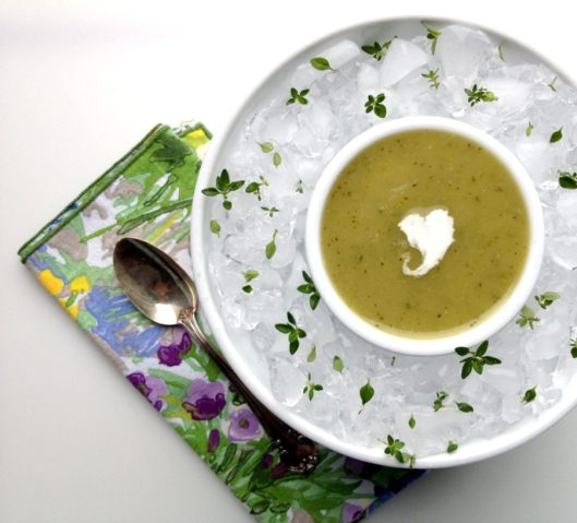Chilled Curried Zucchini Soup with a heart shaped dollop of sour cream in the center.  The soup bowl is sitting in a larger bowl of ice sprinkled with thyme leaves.  There is a floral napkin with a spoon.
