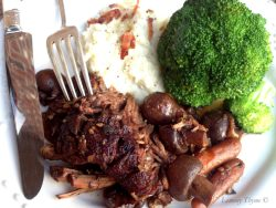 Slow Braised Beef Pot Roast with mashed potatoes and broccoli sitting on white plate. There's a fork and knife on plate.