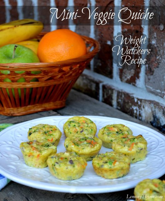 Mini veggie quiche sitting on a white plate with a bowl of fresh whole fruit in the background.