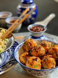Asian Salmon Meatballs over cauliflower fried rice with a sesame soy ginger sauce.