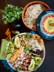 Overhead view of the biggest serving bowl loaded with chicken burrito ingredients