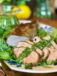 Sliced spice rubbed pork tenderloin with cilantro vinaigrette on a platter