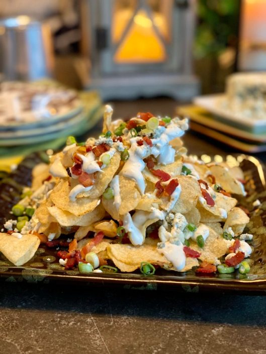 Kettle chips piled with bacon, scallions, blue cheese dressing on a brown plate sitting on a stone table.