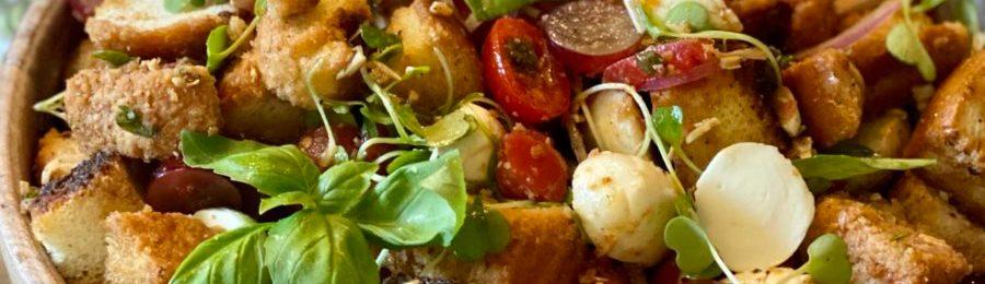 Bruschetta Panzanella Salad featuring rustic bread cubes and fresh mozzarella in a wooden bowl