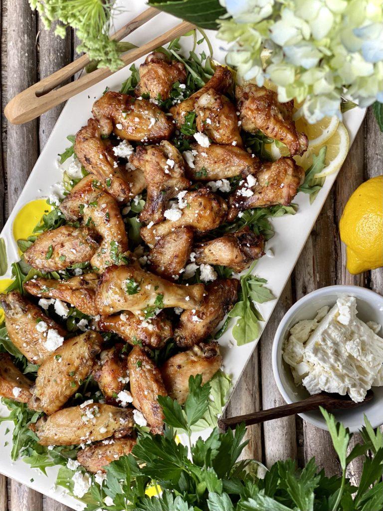 Crispy Greek Chicken Wings with Lemon Garlic & Feta on a white platter on a wooden table.
