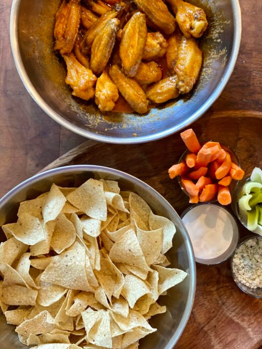 Bowl of tortilla chips. Closeup shot of buffalo chicken wings in metal bowl. Carrot and celery sticks in foreground.