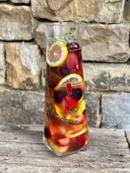 Glass pitcher filled with cut up fresh peaches, strawberries, cherries and lemons sitting on wooden table. Stone wall in background.