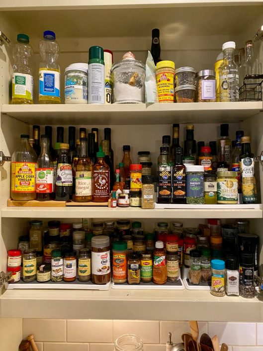 Large spice cabinet with variety of jars and bottles of dried herbs and spices.
