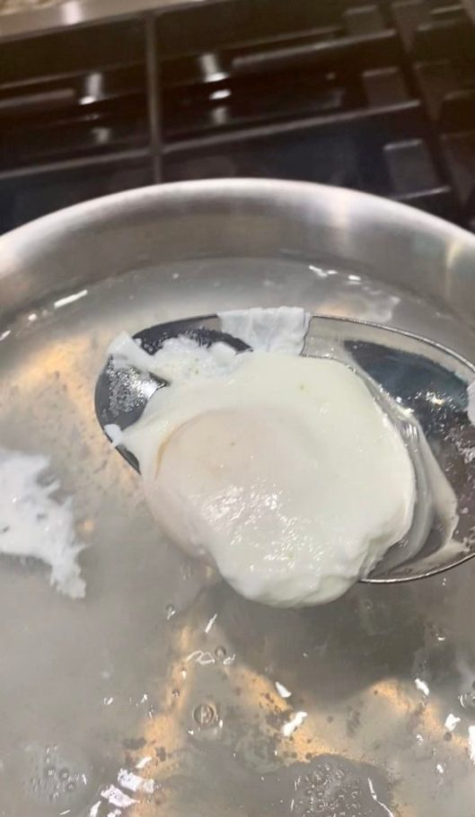 Poached eggs in large pan of simmering water