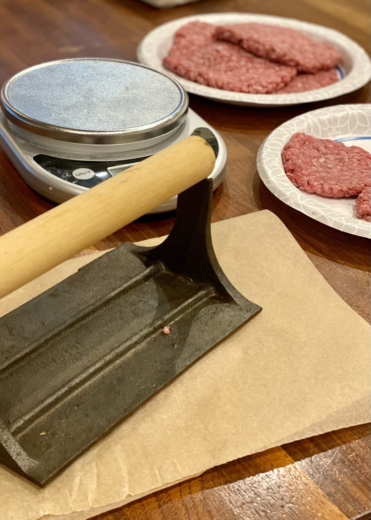 Making smashed all beef burger patties by using parchment paper and a bacon press. Shown with a scale and burgers on a paper plate in the background.