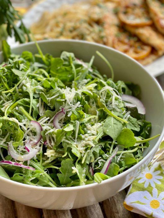 Arugula Salad with Lemon Parmesan Vinaigrette and red onion in a large white bowl.