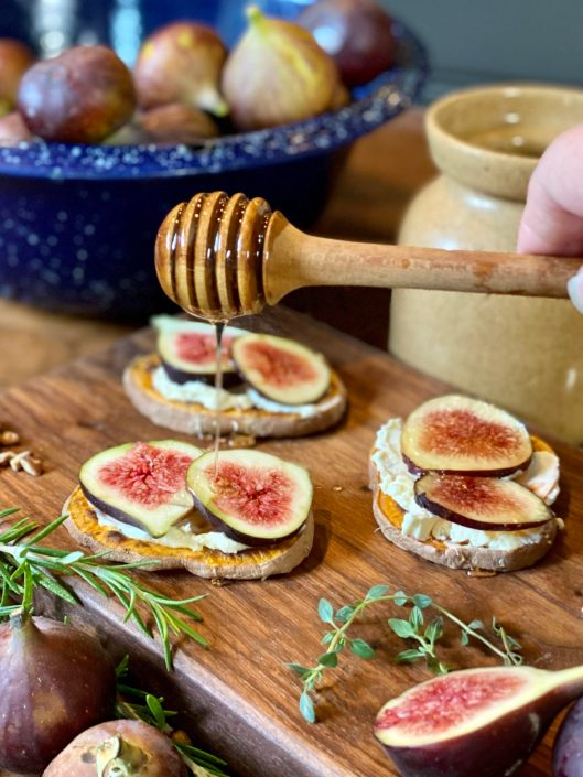 Drizzling honey over sliced figs on sweet potato rounds sitting on wooden cutting board