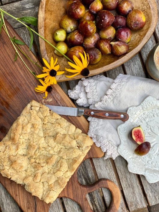 Fresh Fig Crumble Bars on a wooden cutting board with fresh figs and yellow daisies.