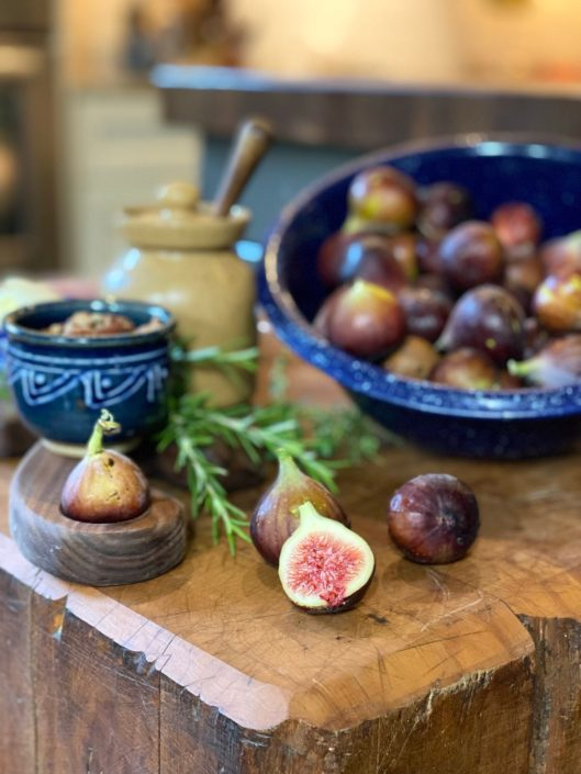 Wooden block table with large bowl of fresh figs and sliced figs