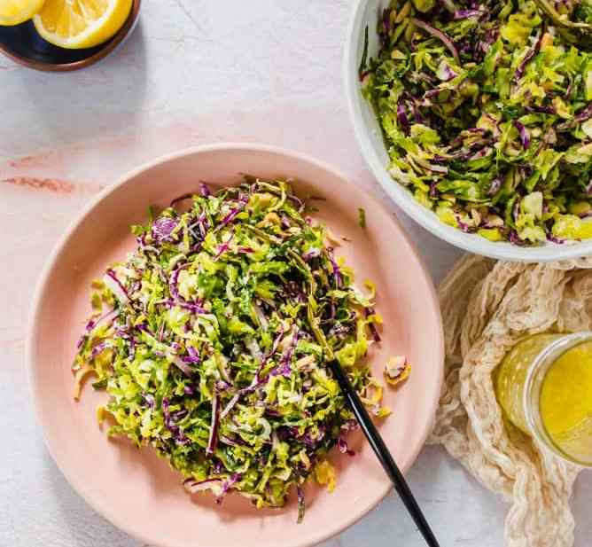 shaved raw brussels sprouts salad in pink and white bowls with lemons and dressing