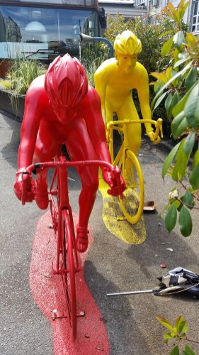a yellow and a red statue of a cyclist
