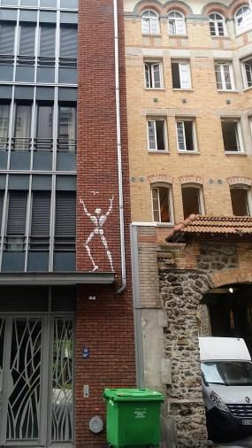 white stick figure graffito catching a butterfly