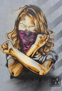A graffito of a girl crossing her arms in front of her body like in a defense move