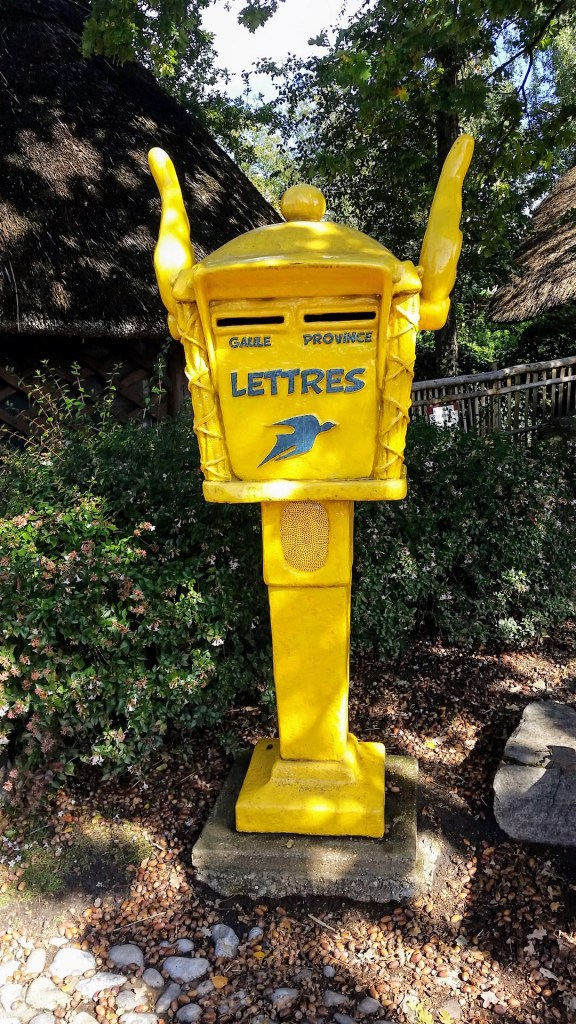 a yellow letterbox decorated with the same wings that are on Asterix' helmet