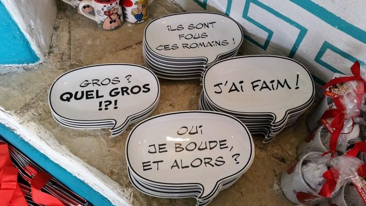 """4 plates shaped like speech bubles saying """"Ils sont fous ces romains"""", """"J'ai faim"""", """"Oui je boude,et alors?"""" and """"Gros, *quel gros?!*!"""