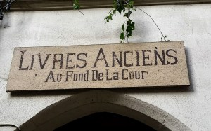 "A sign across a stone portal saying ""Livres anciens au fond de la cour"""